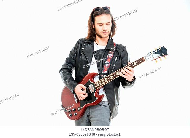 Serious young male guitarist standing and playing electric guitar over white background
