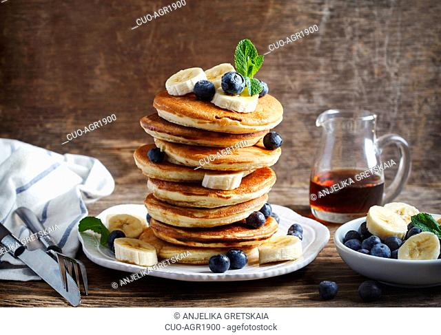 Pancakes with banana, blueberry and maple syrup for breakfast