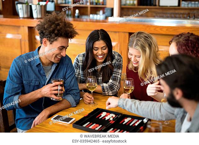 Friends playing backgammon while having drinks in bar