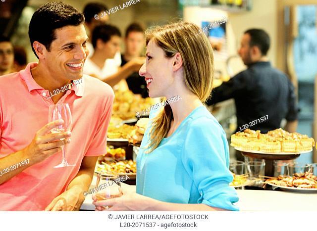 Couple drinking wine and eating tapas. Pintxos. Bar txondorra. Parte Vieja. Old town. San Sebastian. Donostia. Gipuzkoa. Basque Country. Spain