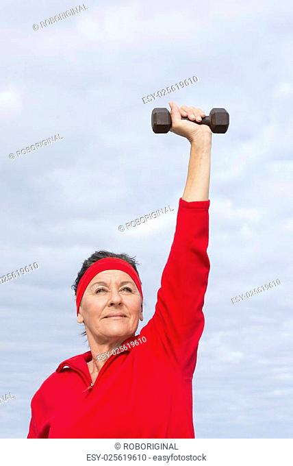 Portrait beautiful middle aged woman showing active retirement, excercising with weights arms up outdoor, positive, confident, energetic, focused