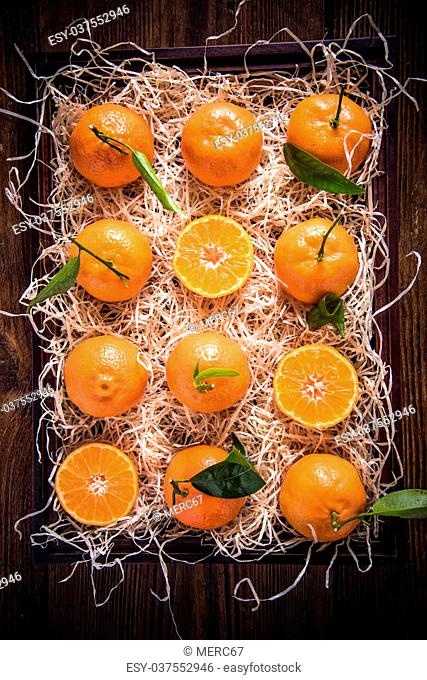 Tangerines in wooden rustic crate from above, whole and half cut