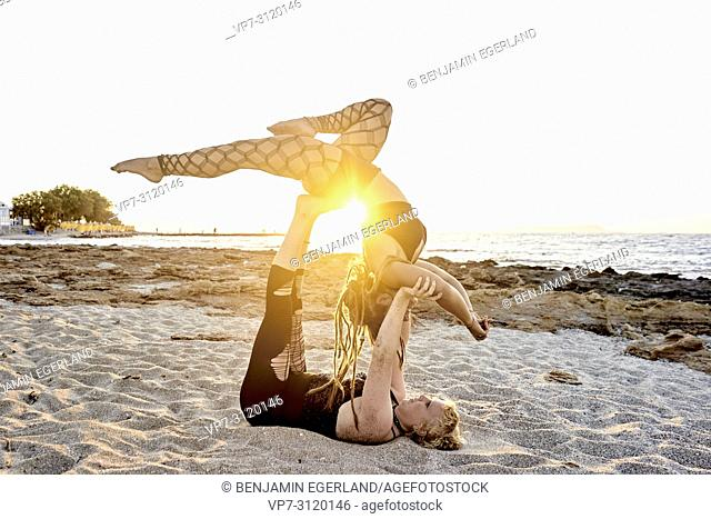 Yoga exercises on beach, Aerial Yoga, in holiday destination Chersonissos, Crete, Greece