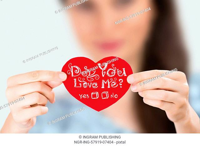 Woman holding red heart with question: Do you love Me?