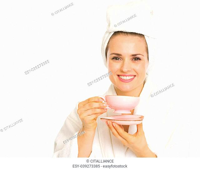 Smiling young woman in bathrobe holding cup of coffee