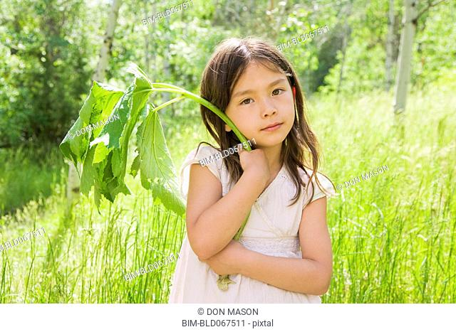 Young Asian girl holding plant stem in field