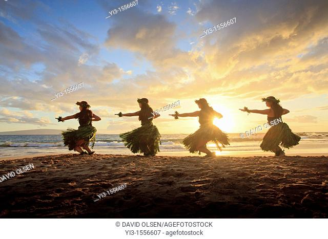Four hula dancers at sunset at Palauea, Maui, Hawaii, backlit by the sun