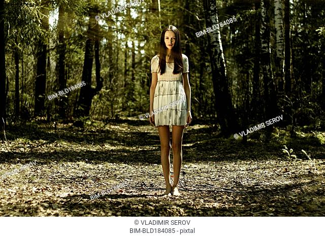Barefoot Caucasian woman standing in forest