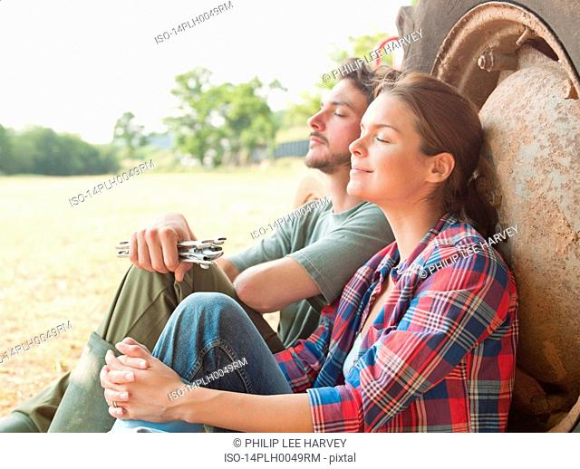 couple sat by tractor eyes closed