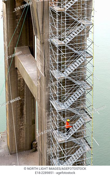 Canada, BC, Surrey. Worker climbing temporary construction stairway attached to the pillar of the old Port Mann Bridge