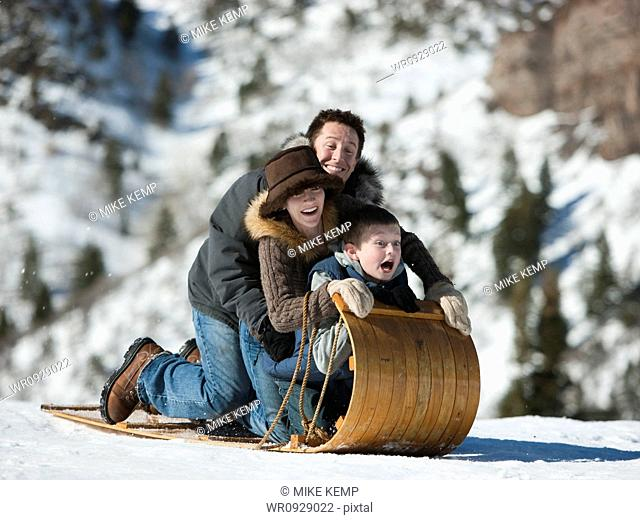 USA, Utah, Big Cottonwood Canyon, parents and son 10-11 tobogganing in mountains