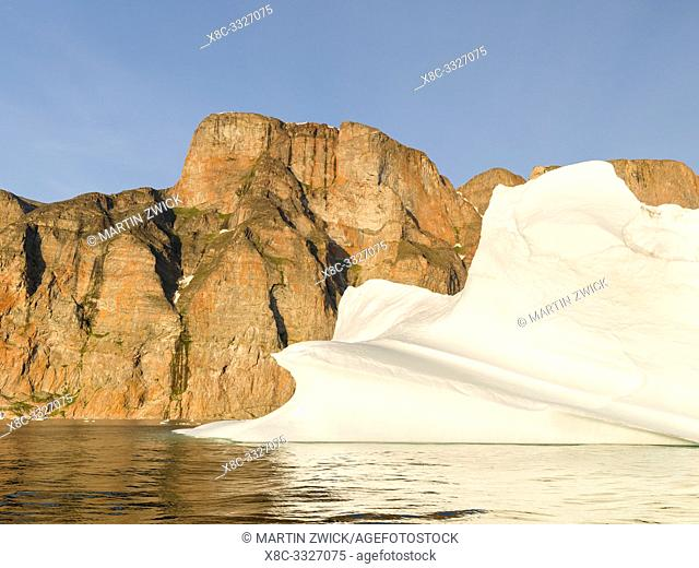 Iceberg in the Uummannaq Fjord System. Red cliffs of Storoen island in the background. America, North America, Greenland, Denmark