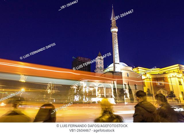 Traffic light Trails and people next to Ethem Bey Mosque at night. Tirana, Albania