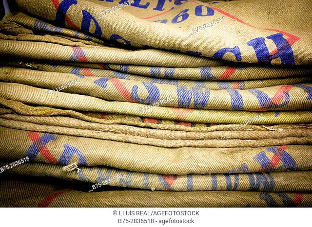 Pile of coffee burlap sacks with colored texts, folded