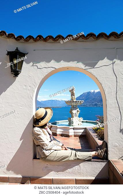 Woman with straw hat relax in an arch with a water fountain over alpine lake Maggiore with snow-capped mountain in a sunny day in Ticino, Switzerland