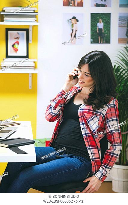 Female fashion blogger telephoning at her office