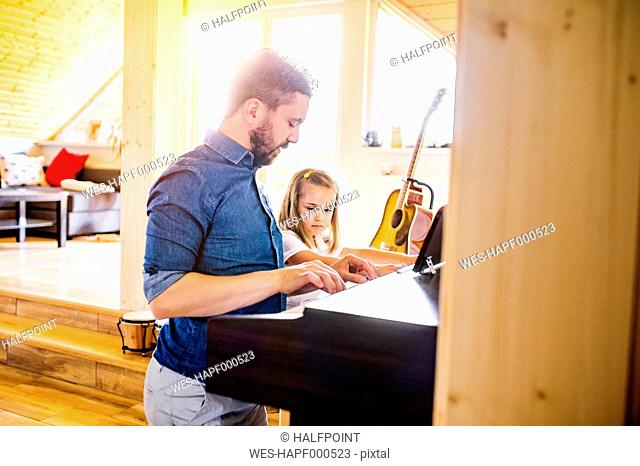Father and daughter making music together