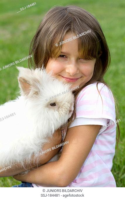 Girl (7 years old) with a dwarf teddy rabbit in her arms. Germany