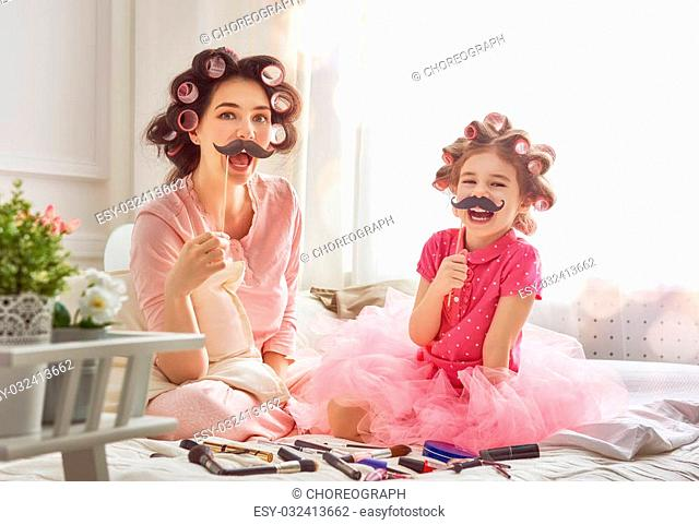 Funny family! Mother and her child daughter girl with a paper accessories. Mother and daughter preparing for a party and having fun