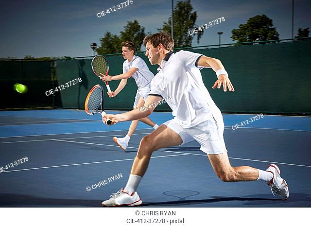 Young male tennis doubles players playing tennis, hitting the ball on blue tennis court