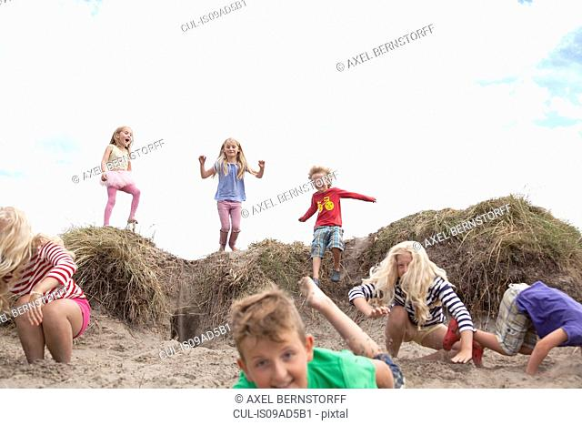 Group of children jumping off sand dunes, Wales, UK