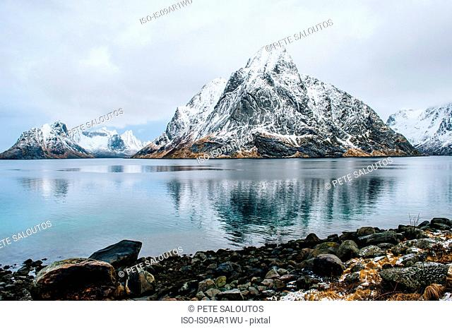 View of snow capped mountain and rocky coastline, Reine, Lofoten, Norway