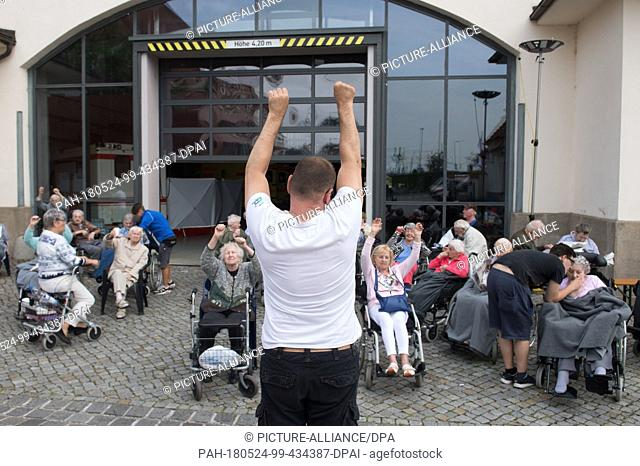 24 May 2018, Germany, Dresden: Residents effected by the evacuation in Dresden sitting during morning gymanstics at the site of the Dresden messe in an...