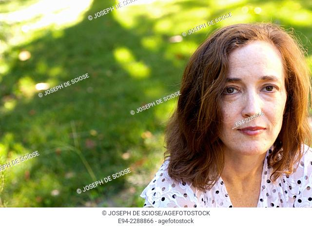 Portrait of a 38 year old redheaded woman outdoors looking at the camera