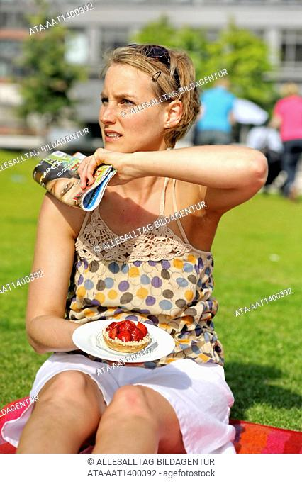Woman eating a cake and is disturbed by a wasp