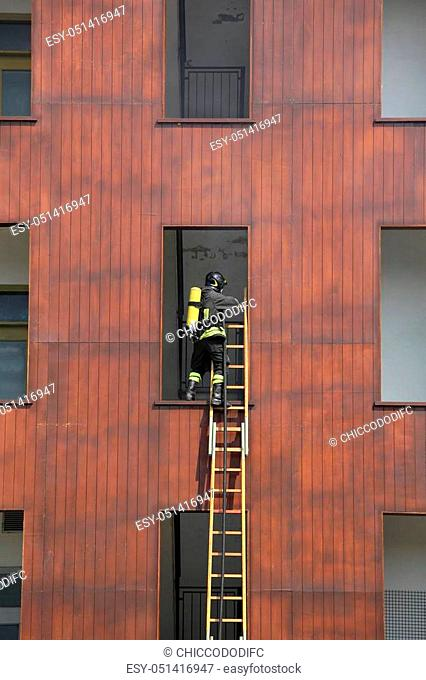 Firefighter on the wooden ladder enters the window in the fire station on the high building called Castle of Maneuver