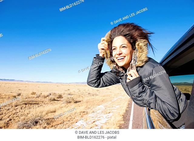 Hispanic woman leaning out car window