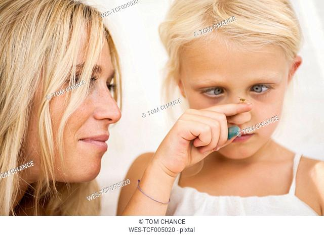 Cross-eyed little girl watching fly sitting on her finger
