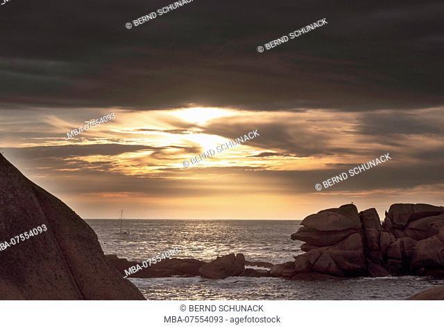Pink Granite Coast with impressive pink granite rocks near Ploumanac'h, evening sun below rain clouds
