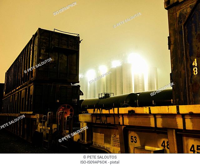 Misty view of industrial storage tanks between freight locomotive at night, Seattle, Washington, USA