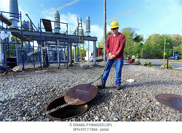 Power engineer accessing manhole cover at high voltage power distribution station, Braintree, Massachusetts, USA