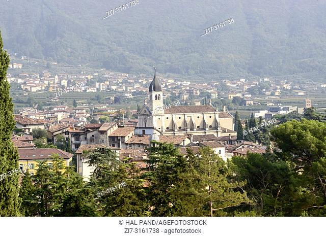 view of parish Assunta church in little historical town , shot from above in bright fall light at Arco, Trento, Italy