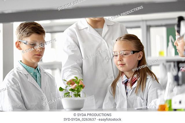 students and teacher with plant at biology class