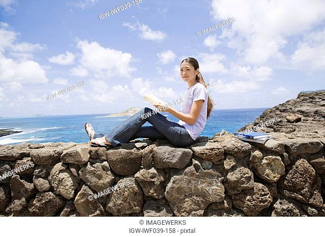 View of a young woman sitting on rock with book