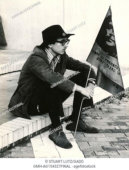 A male student wearing hippie attire, including thick glasses and a fedora hat, sits on a step and holds a flag with the face of revolutionary Che Guevara...