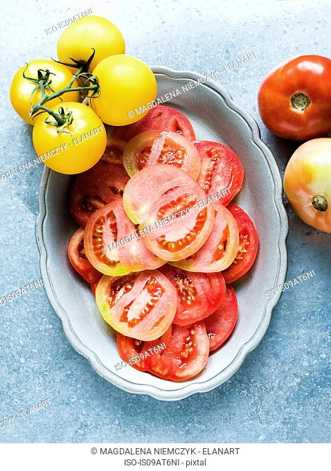 Still life of red sliced tomatoes in dish and yellow vine tomatoes