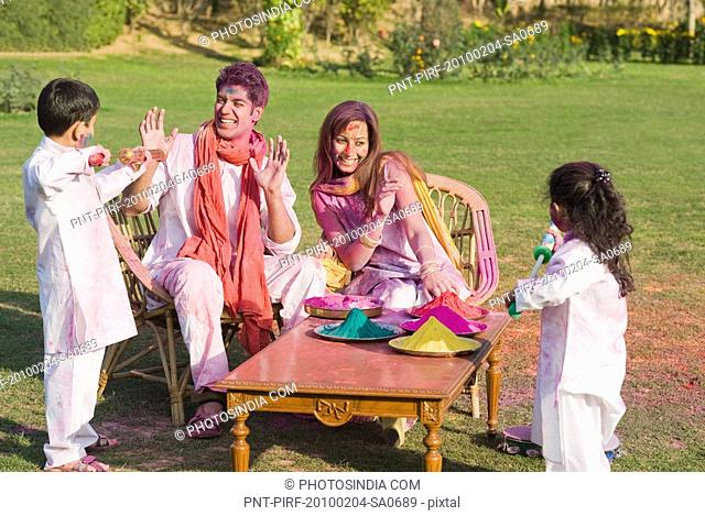 Family celebrating Holi with colors