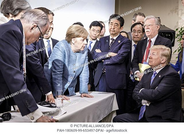 HANDOUT - 09 June 2018, Charlevoix, La Malbaie, Quebec, Canada: German Chancellor Angela Merkel (CDU, C) speaking with US President Donald Trump (r) during...