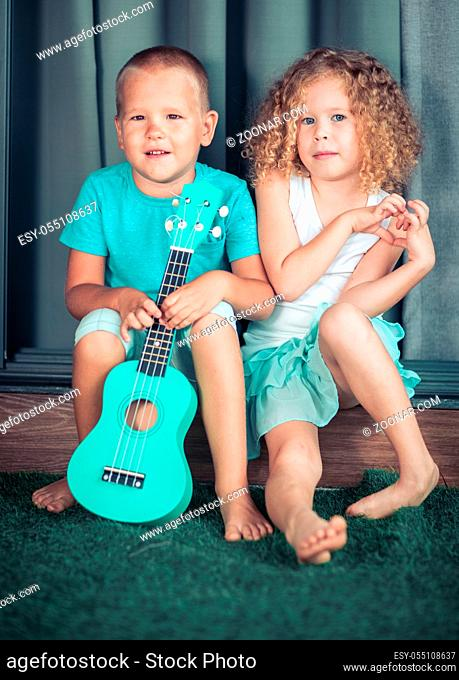 Portrait of a cute kids sitting ouddoor with ukulele