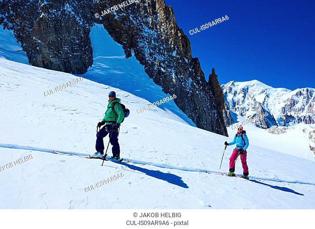 Mature male and female skiers moving up Mont Blanc massif, Graian Alps, France