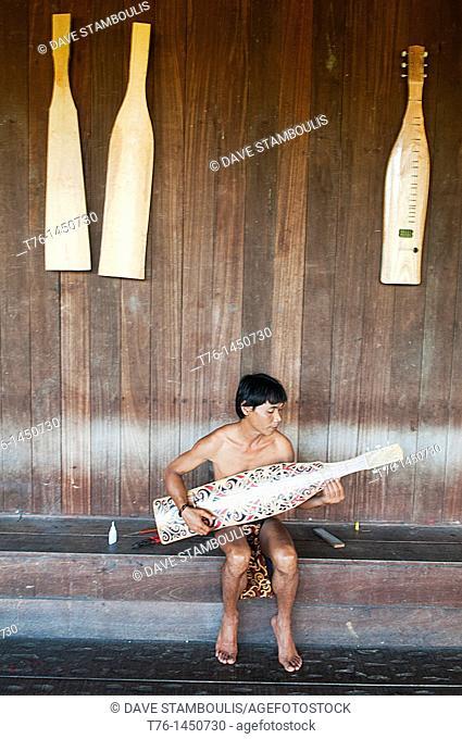 Orang Ulu man plays his traditional sape in Sarawak, Borneo, Malaysia