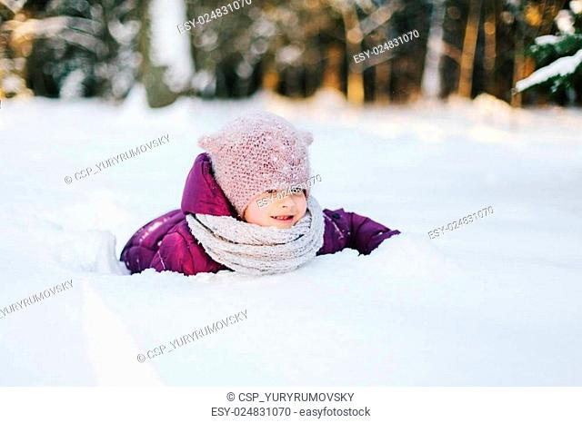 Little girl playing in snowy park