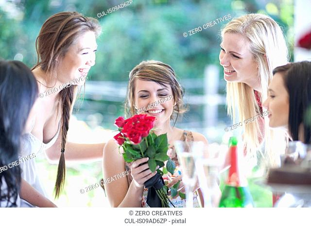 Young woman and friends with bunch of roses