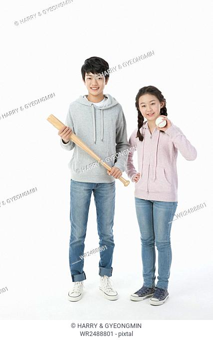 Smiling school boy and school girl standing with a baseball bat and baseball