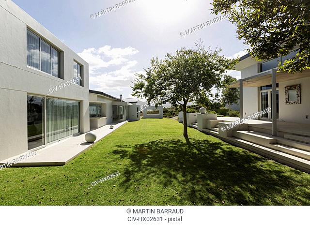 Sunny modern luxury home showcase exterior with grass courtyard