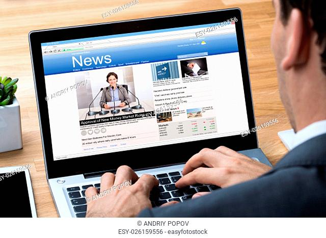 Cropped image of businessman reading news on laptop at office desk